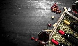 κόκκινο κρασί γυαλιού ανασκόπησης Κόκκινο κρασί σε ένα παλαιό κιβώτιο με ένα ανοιχτήρι Στοκ Εικόνες