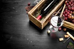 κόκκινο κρασί γυαλιού ανασκόπησης Κόκκινο κρασί σε ένα παλαιό κιβώτιο με ένα ανοιχτήρι Στοκ Φωτογραφία