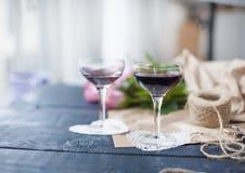κόκκινο κρασί δύο γυαλιών Μια ανθοδέσμη των ρόδινων τριαντάφυλλων στο καφετί έγγραφο Μακαρόνια ζύμης χρώματος κοντά στο παράθυρο  Στοκ φωτογραφίες με δικαίωμα ελεύθερης χρήσης
