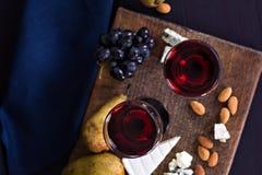 Κόκκινο κρασί και πρόχειρα φαγητά Κρασί, σταφύλια, τυρί, καρύδια, ελιές Ρομαντικό βράδυ, ακόμα ζωή Στοκ φωτογραφία με δικαίωμα ελεύθερης χρήσης