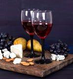 Κόκκινο κρασί και πρόχειρα φαγητά Κρασί, σταφύλια, τυρί, καρύδια, ελιές Ρομαντικό βράδυ, ακόμα ζωή Στοκ Εικόνες