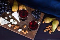 Κόκκινο κρασί και πρόχειρα φαγητά Κρασί, σταφύλια, τυρί, καρύδια, ελιές Ρομαντικό βράδυ, ακόμα ζωή Στοκ Φωτογραφία