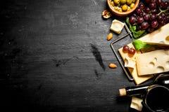 Κόκκινο κρασί με το ευώδη τυρί, τις ελιές και τα αμύγδαλα Στοκ Φωτογραφίες