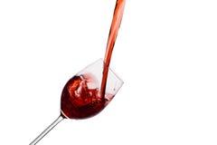Κόκκινο κρασί που χύνεται σε ένα γυαλί κρασιού στοκ εικόνα