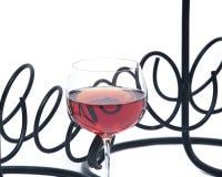 Κόκκινο κρασί ροδιών στον κάτοχο μπουκαλιών κρασιού γυαλιού και μετάλλων Στοκ Εικόνες