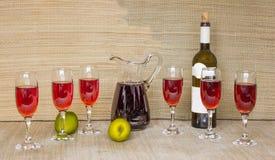 Κόκκινο κρασί στα γυαλιά και το φυσικό υπόβαθρο συντρόφων χλόης μπουκαλιών Στοκ Εικόνα