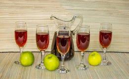 Κόκκινο κρασί στα γυαλιά και το φυσικό υπόβαθρο συντρόφων χλόης μπουκαλιών Στοκ Φωτογραφίες