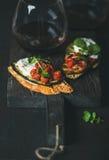Κόκκινο κρασί στο γυαλί και το brushetta με τα λαχανικά, κρέμα-τυρί, arugula Στοκ φωτογραφία με δικαίωμα ελεύθερης χρήσης