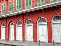 Κόκκινο κτήριο - άσπρες πόρτες - πράσινη γαλλική συνοικία παραθυρόφυλλων Στοκ Φωτογραφία