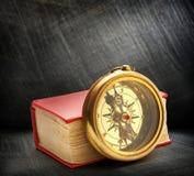 Κόκκινο κλειστό βιβλίο με την αναδρομική πυξίδα Στοκ Εικόνες