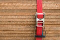 Κόκκινο λουρί αναστολέων που καθορίζει τους ξύλινους πίνακες/τις ξύλινες σανίδες Στοκ Εικόνα