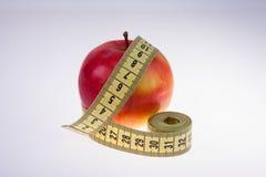 Κόκκινο μέτρο μήλων και ταινιών σχετικά με το άσπρο υπόβαθρο Στοκ Φωτογραφίες