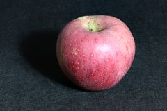 Κόκκινο μήλο στο μαύρο πάτωμα υποβάθρου είναι τα στρογγυλά φρούτα ενός δέντρου της ροδαλής οικογένειας Στοκ φωτογραφία με δικαίωμα ελεύθερης χρήσης