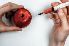 Κόκκινο μήλο με μια υποδερμική σύριγγα βελόνων Στοκ Εικόνες