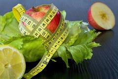 Κόκκινο μήλο με τη μέτρηση της ταινίας φύλλα της σαλάτας πάγου Στοκ Εικόνες