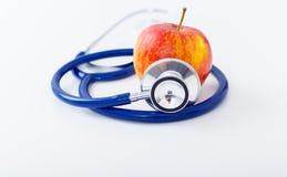 Κόκκινο μήλο με το στηθοσκόπιο στο άσπρο υπόβαθρο Στοκ Εικόνες