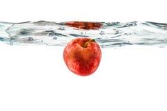 Κόκκινο μήλο που πέφτουν στο νερό με τον παφλασμό νερού σε ένα άσπρο BA Στοκ Εικόνες