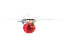 Κόκκινο μήλο που πέφτουν στο νερό με τον παφλασμό νερού σε ένα άσπρο BA Στοκ Εικόνα