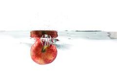 Κόκκινο μήλο που πέφτουν στο νερό με τον παφλασμό νερού σε ένα άσπρο BA Στοκ Φωτογραφίες