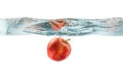 Κόκκινο μήλο που πέφτουν στο νερό με τον παφλασμό νερού σε ένα άσπρο BA Στοκ εικόνα με δικαίωμα ελεύθερης χρήσης