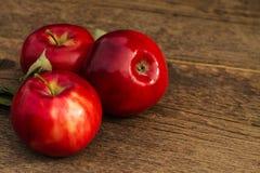 Κόκκινο μήλο σε ένα θολωμένο υπόβαθρο των μήλων Στοκ Φωτογραφίες