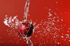 Κόκκινο μήλο σε ένα κόκκινο υπόβαθρο Στοκ εικόνα με δικαίωμα ελεύθερης χρήσης