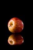 Κόκκινο μήλο σε ένα μαύρο αντανακλαστικό υπόβαθρο Στοκ Φωτογραφία