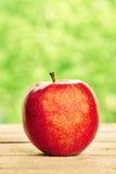 Κόκκινο μήλο στον ξύλινο πίνακα Στοκ Φωτογραφίες