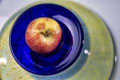 Κόκκινο μήλο στο αρχικό μπλε κυκλικό πιάτο Στοκ εικόνα με δικαίωμα ελεύθερης χρήσης