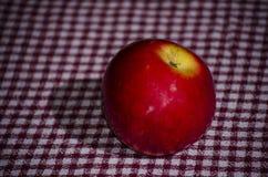 Κόκκινο μήλο στο επιτραπέζιο ύφασμα Στοκ Εικόνες
