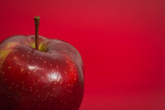 Κόκκινο μήλο στο κόκκινο υπόβαθρο Στοκ εικόνες με δικαίωμα ελεύθερης χρήσης
