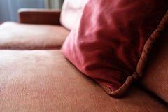 Κόκκινο μαξιλάρι σε έναν καναπέ με armrest των επικαλυμμένων επίπλων Στοκ φωτογραφία με δικαίωμα ελεύθερης χρήσης