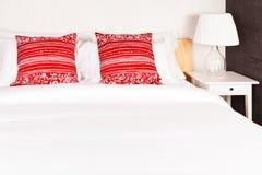 Κόκκινο μαξιλάρι στην κρεβατοκάμαρα με το άσπρους σεντόνι και το λαμπτήρα Στοκ Εικόνες