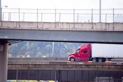 Κόκκινο μεγάλο ημι φορτηγό εγκαταστάσεων γεώτρησης με την ξηρά οδήγηση ρυμουλκών φορτηγών ημι στο lowe Στοκ Εικόνα