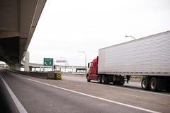 Κόκκινο μεγάλο ημι φορτηγό εγκαταστάσεων γεώτρησης με το μακρύ ρυμουλκό σημαιοφόρων που μεταφέρει για Στοκ Εικόνες