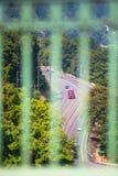 Κόκκινο μεγάλο ημι φορτηγό εγκαταστάσεων γεώτρησης με το ρυμουλκό που κινείται με το τύλιγμα του πράσινου δρόμου Στοκ Εικόνες