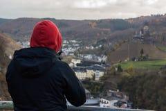 Κόκκινο με κουκούλα άτομο που κοιτάζει πέρα από την του χωριού κοιλάδα Στοκ Εικόνες