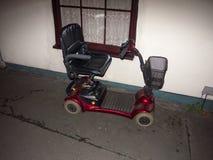 κόκκινο μηχανικό δίκυκλο κινητικότητας που σταθμεύουν έξω μπροστά από την ανικανότητα σπιτιών στοκ εικόνα με δικαίωμα ελεύθερης χρήσης