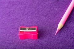 Κόκκινο μολύβι με τη ξύστρα για μολύβια στο ιώδες υπόβαθρο χαρτικά Στοκ φωτογραφίες με δικαίωμα ελεύθερης χρήσης