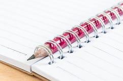 Κόκκινο μολύβι κινηματογραφήσεων σε πρώτο πλάνο στο σημειωματάριο Στοκ φωτογραφία με δικαίωμα ελεύθερης χρήσης