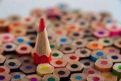 Κόκκινο μολύβι μεταξύ των ζωηρόχρωμων κραγιονιών Στοκ Εικόνες