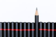 Κόκκινο μολύβι που ξεχωρίζει από το πλήθος των ίδιων συνεργατών αφθονίας Στοκ Εικόνες
