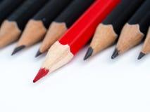 Κόκκινο μολύβι που ξεχωρίζει από το πλήθος των ίδιων συνεργατών αφθονίας Στοκ εικόνα με δικαίωμα ελεύθερης χρήσης