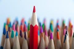 Κόκκινο μολύβι στο υπόβαθρο των ζωηρόχρωμων κραγιονιών Στοκ Εικόνες