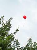 Κόκκινο μπαλόνι που επιπλέει στον ουρανό Στοκ φωτογραφία με δικαίωμα ελεύθερης χρήσης