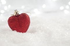 Κόκκινο μπιχλιμπίδι καρδιών Χριστουγέννων σε μια ανασκόπηση χιονιού Στοκ Εικόνα