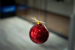 Κόκκινο μπιχλιμπίδι Χριστουγέννων με ένα τόξο στην κορυφή Στοκ Εικόνα