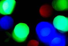 Κόκκινο, μπλε και πράσινο φως θαμπάδων στο σκοτεινό υπόβαθρο για την έννοια Χριστουγέννων Στοκ Εικόνα