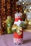 Κόκκινο μπουκάλι που διακοσμείται με το φωτεινό ύφος Χριστουγέννων Στοκ φωτογραφία με δικαίωμα ελεύθερης χρήσης