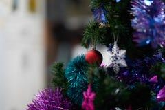 Κόκκινο ντεκόρ μπιχλιμπιδιών στο χριστουγεννιάτικο δέντρο με ζωηρόχρωμο snowflake Στοκ εικόνα με δικαίωμα ελεύθερης χρήσης
